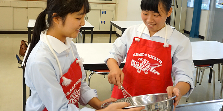 붉은 에이프런으로 요리를 하는 후루카와씨(왼쪽)과 야마가타씨( 오른쪽)
